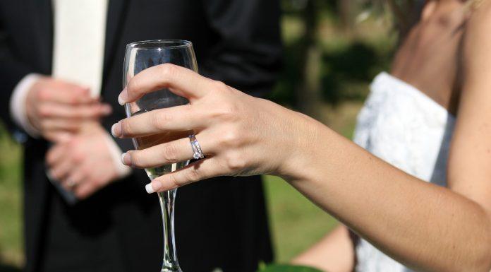 Una pareja de recién casados brindan con una copa de vino