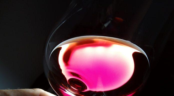 Una copa inclinada de vino rosado