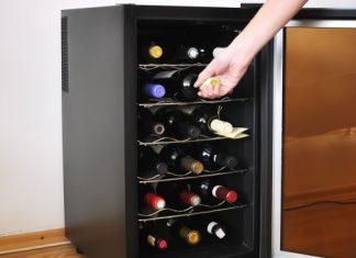 mano guardando vino en una vinoteca nevera pequeña